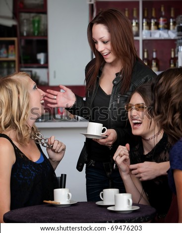 Foursome of young cute teen friends laughing at a cafe - stock photo