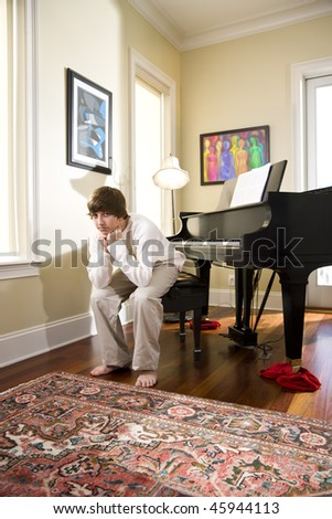 Fourteen year old teenage boy at home sitting on piano bench - stock photo