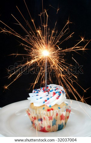 Fourth of July cupcake done with red and blue star shaped sprinkles and a sparkler firework as the candle. - stock photo