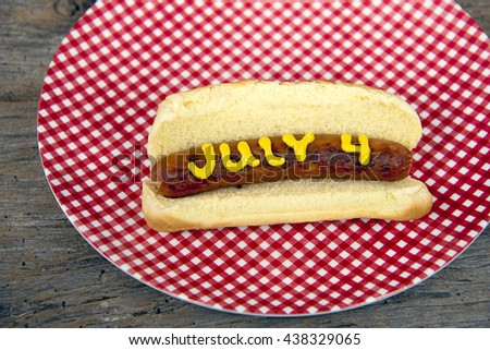 Fourth of July hot dog in bun with yellow mustard on red and white gingham plate on rustic barn wood. - stock photo