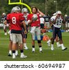 FOXBOROUGH, MA - AUGUST 6: Tom Brady has a break during a practice at the training camp in Foxborough MA. August 2010. Tom Brady is in the center of the image has his helmet ind right hand. - stock photo