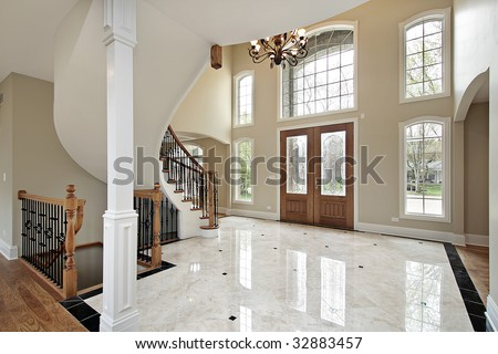 Foyer and circular staircase in new construction home - stock photo