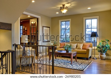 Foyer entrance of home showing lounge seating, stair railing, and wood floors. - stock photo