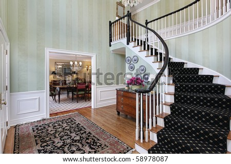 Foyer in luxury home with carpeted staircase - stock photo