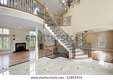 Foyer with curved staircase in luxury home - stock photo