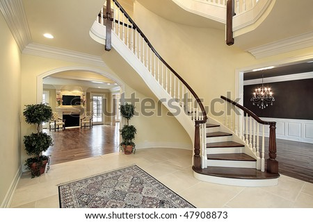 Foyer with curved staircase in new construction home - stock photo