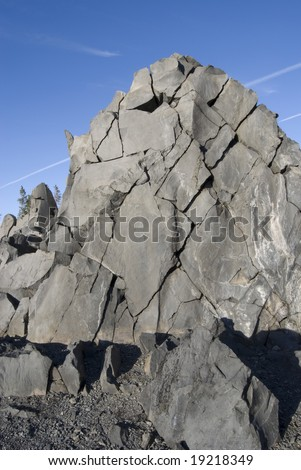Fractured Rockface against a bright blue sky.  Near McKenzie Summit at view point, Oregon. - stock photo