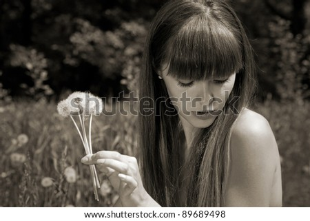 fragile girl holding dandelions in hand. blowball