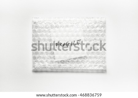 fragile, handwriting on white square paper in bubble pack, white paper background