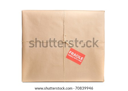 Fragile package wrapped in brown craft paper with label and string on it - stock photo