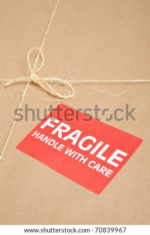 Fragile package wrapped in brown craft paper with label, tag and string on it, - stock photo