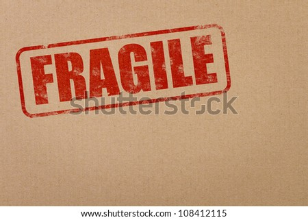 Fragile stamp on a cardboard package with copy space - stock photo