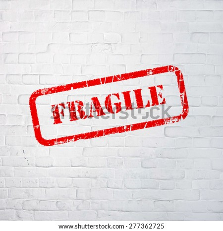 fragile stamp style sign printed on the wall - stock photo