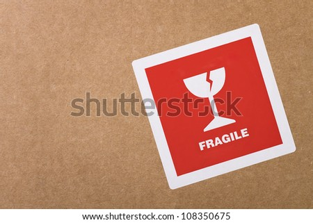 Fragile sticker at the cardboard box with copy space - stock photo