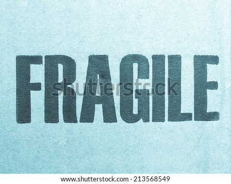 Fragile warning sign label tag on a cardboard box packet parcel for mail post shipping - cool cyanotype - stock photo