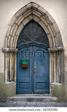 Fragment an ancient build with blue Gothic  wooden door - stock photo