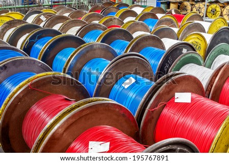 Fragment inside a modern plant producing power electric cable and optical fiber. Interior of modern production line. Finished goods on container cable reels for transportation and sale of consumer  - stock photo