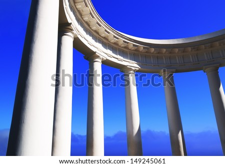 Fragment of a beautiful white colonnade with pattern and the blue sky in the evening in the Crimea, Ukraine