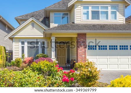 Fragment of a custom built luxury house with nicely trimmed and designed front yard, lawn in a residential neighbourhood in Canada. Front entrance. - stock photo