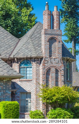 Fragment of a expensive brick house with nicely trimmed front yard and lawn. Chimney and window view. - stock photo
