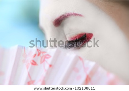 Fragment of a face of young woman with geisha style makeup - stock photo