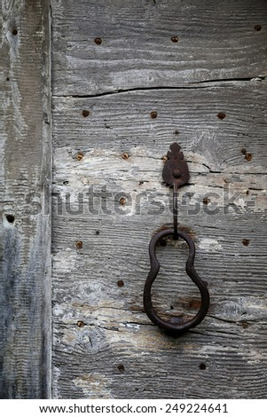 Fragment of a fortified medieval wooden door with hardware elements - stock photo