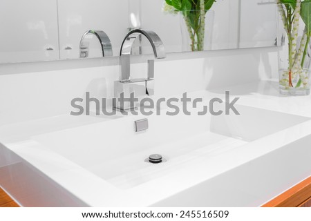 Fragment of a luxury bathroom. View of a white modern sink. - stock photo