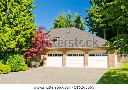 Fragment of a luxury house with a triple garage door in Vancouver, Canada. - stock photo