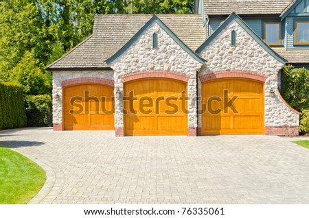 Fragment of a luxury house with triple garage door in Vancouver, Canada. - stock photo