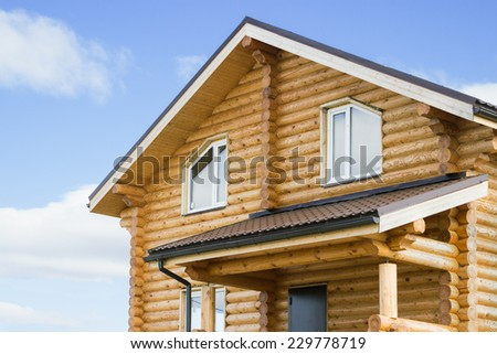 Fragment of a new log cabin against the sky - stock photo