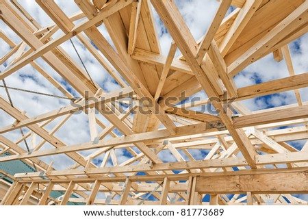 Fragment of a new residential construction home framing against a blue sky