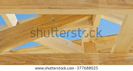 Fragment of a new residential construction home framing against a blue sky.Local focus - stock photo