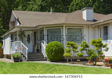 Fragment of a nice house with entrance door and landscape in the front. Vancouver, Canada - stock photo
