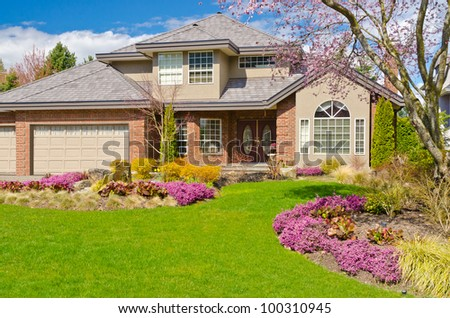 Fragment of a nice house with gorgeous lawn and outdoor landscape in Vancouver, Canada. - stock photo