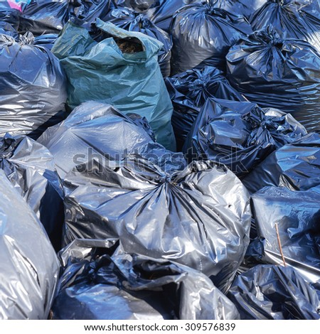 Fragment of a pile of black plastic garbage bags - stock photo