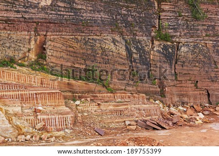 Fragment of a quarry with a vertical wall of sandstone, revealing numerous geological layers  - stock photo