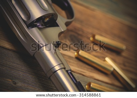 fragment of a revolver Nagan with one bullet in the drum for game Russian roulette. instagram image filter retro style - stock photo