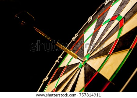 Fragment of a sisal dartboard with a dart hitting an bullseye on a black background (concept)
