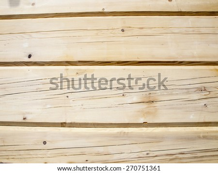 fragment of a wall from wooden logs as background - stock photo