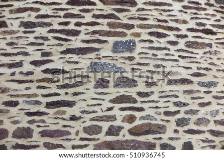 Fragment of a wall of stone with irregular shapes and broad joints as a background