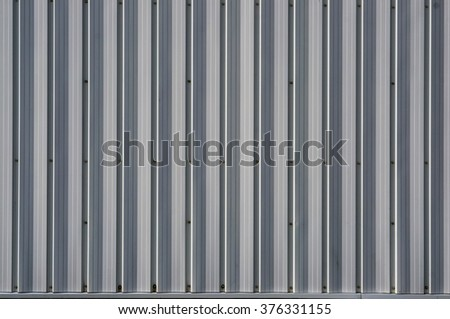Fragment of a white metal corrugated wall of a rural warehouse or shed - stock photo