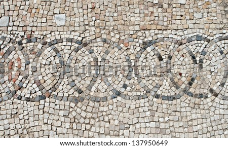 Fragment of an ancient  floor mosaic. Colorful small tiles and stones, unusual geometric ornament, regular forms.Euthemius Monastery. Israel - stock photo