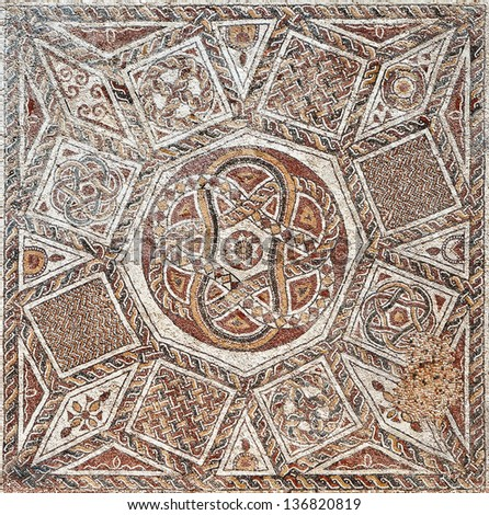 Fragment of an ancient  floor mosaic. Colorful small tiles, unusual geometric ornament, floral and regular forms. Roman fortress. Israel - stock photo