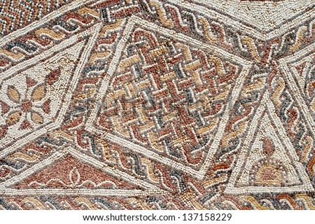 Fragment of an ancient  floor mosaic. Colorful small tiles, unusual geometric ornament, floral and regular forms. Israel - stock photo