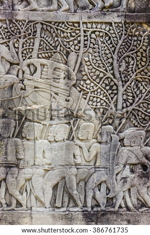 Fragment of ancient Khmer art carving bas-relief showing Hindu legend scenes on the wall of Bayon temple, Siem Reap, Cambodia. - stock photo