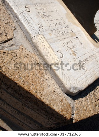 Fragment of ancient stone dial sundial closeup. On the white marble slab engraved numbers and names of the months in Russian - stock photo