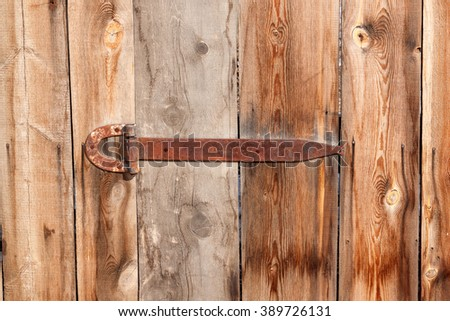 Fragment of ancient wooden door with old lock with  the old barn hanging on long iron hinge - stock photo
