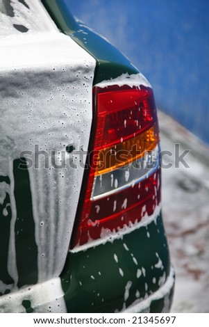 Fragment of automobile in soapsuds on washing - stock photo