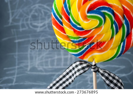 Fragment of big colorful lollipop with checkered ribbon. - stock photo