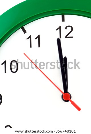 Fragment of big wall clock with green case shows almost twelve o'clock isolated on white closeup - stock photo